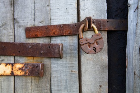 Old rusty padlock on wooden grey background photo