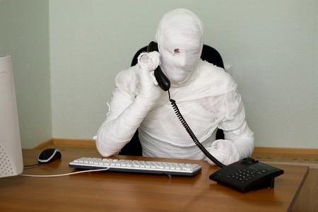 speaking tube: Businessman mummy talking on telephone on white  Stock Photo