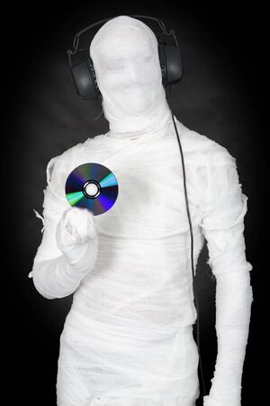 Man in bandage with ear-phones and disc on black Stock Photo - 4310911