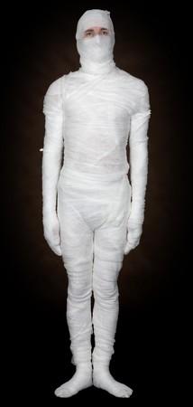 mummified: Man in bandage on the black background
