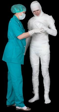 Man in bandage and nurse on black background Stock Photo - 4336570