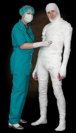 Man in bandage and nurse with stethoscope on black Stock Photo - 4336601