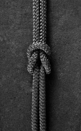 Korn: Bend knot on black cord on the black fabric background Stock Photo
