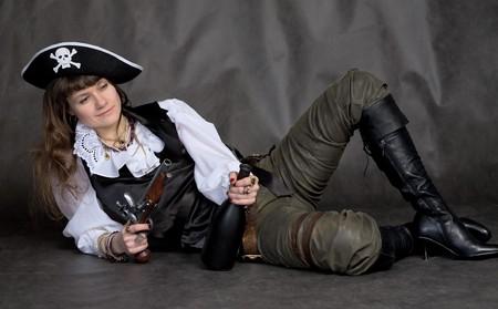 Drunken girl - pirate on black with pistol and bottle photo