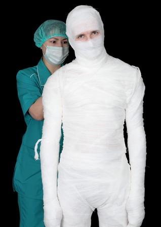 Man in bandage and nurse on black background Stock Photo - 4403546
