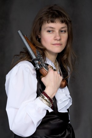 dreary: The sad girl - pirate with ancient pistol in hand on a black background
