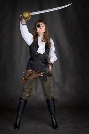 The girl - pirate with a sabre in hands and eye patch on face photo