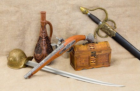 rapier: Stil life with bottle, rapier, sword, pistol and chest Stock Photo