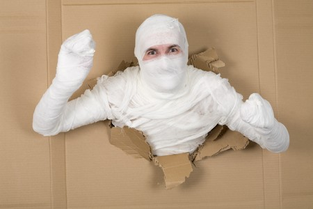 identified: Man in costume mummy looking through hole in cardboard Stock Photo
