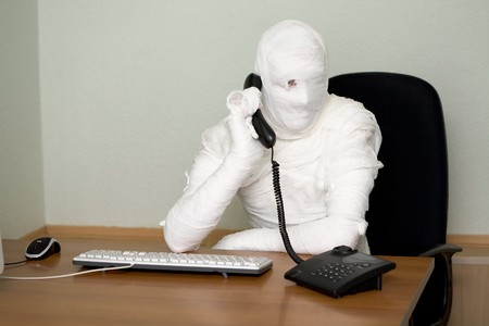 silvery: Bandaged boss calling on telephone in office Stock Photo