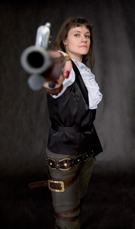 The girl - pirate with ancient pistol in hand on a black background photo