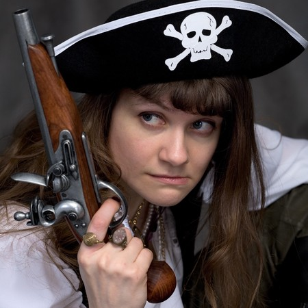Girl - pirate on black with pistol in hand photo