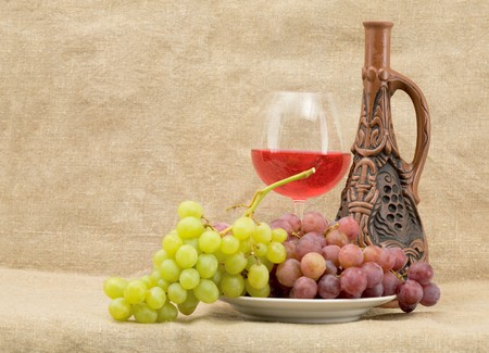 Bright still life with grapes and wine on sacking background photo