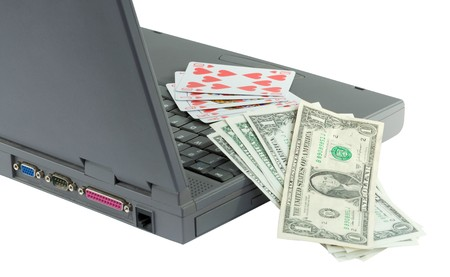Laptop, playing cards and dollars on the white photo