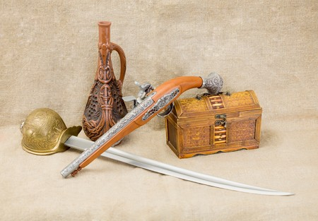 rapier: Still life with bottle, rapier, sword, pistol and chest
