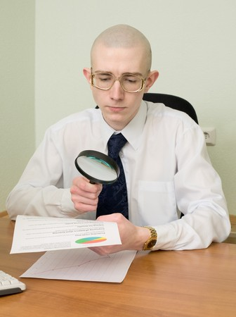 The boss with a magnifier in a hand on a workplace Stock Photo - 4503483