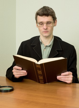The guy in eyeglasses reads the book photo
