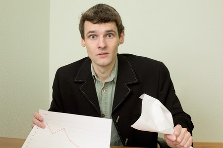 emotionality: The clerk at office sits at a desktop with financial graph Stock Photo