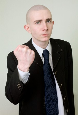 emotionality: The young man in a suit threatens with a fist