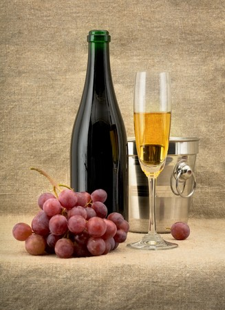 Still life with champagne bottle, grape and goblet on canvas background Stock Photo - 4532934