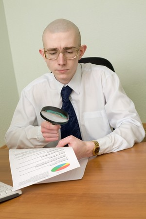 The boss with a magnifier in a hand on a workplace photo