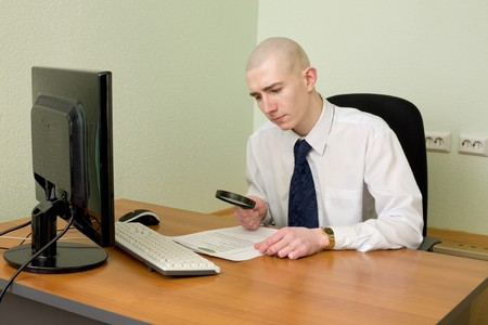 The businessman with a magnifier in a hand on a workplace photo