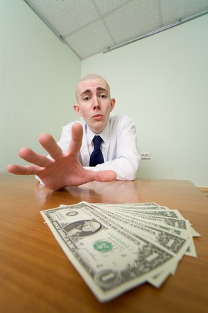 Young man reaches for a batch of money lying on a table photo