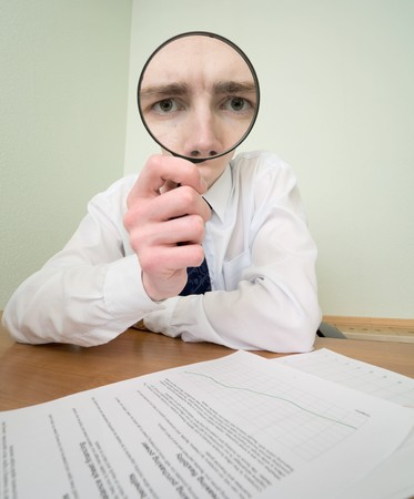 The guy looks through the big magnifier photo