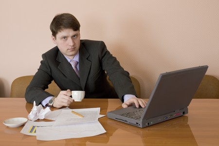 Businessman on a workplace with the laptop and a coffee cup Stock Photo - 4555632