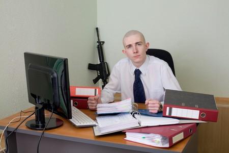rifleman: El jefe de una camisa blanca en un lugar de trabajo con un rifle sobre un fondo Foto de archivo