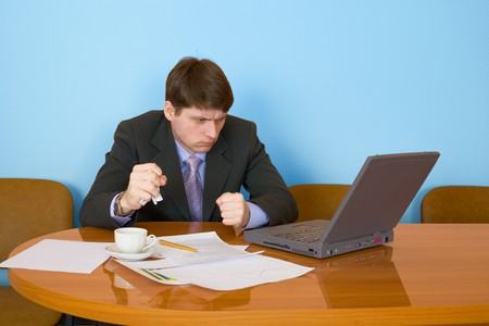 Businessman on a workplace with the laptop and a coffee cup Stock Photo - 4564781