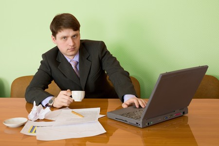Businessman on a workplace with the laptop and a coffee cup Stock Photo - 4570433