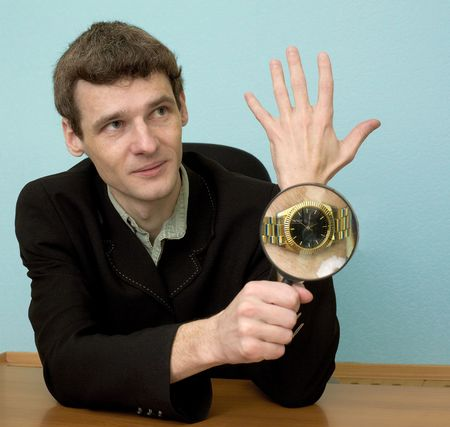 increased: Person examines a watch through a magnifier Stock Photo