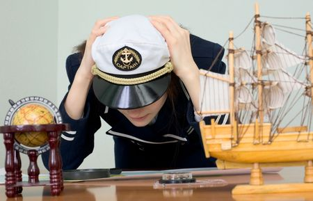 vexation: The sad woman in a sea uniform at table Stock Photo