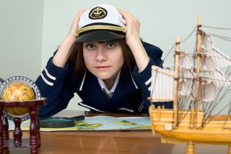 scared girl: Scared girl in sea uniform at a table with map