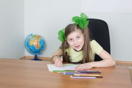 The girl sitting at a table with color pencils photo