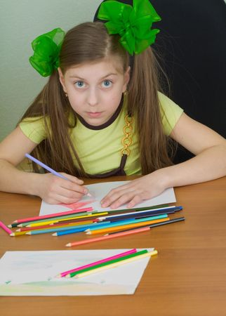 Little girl drawing sitting at a table photo