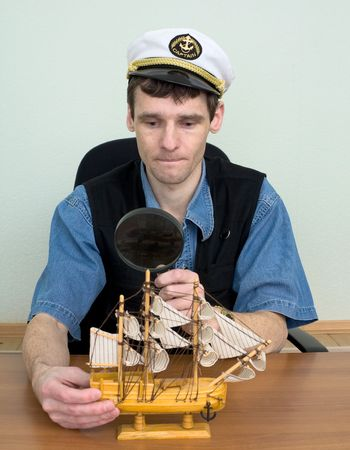 Guy in a sea cap examines a toy sailing vessel photo