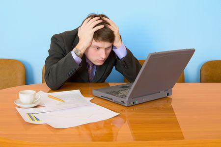 uneasiness: Hombre de negocios en un lugar de trabajo con la computadora port�til y una taza de caf�