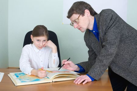 Tutor in a suit and schoolgirl with atlas photo