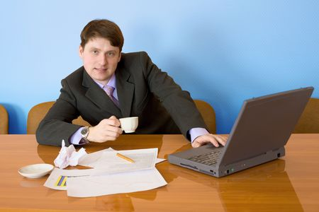 Businessman on a workplace with the laptop and a coffee cup Stock Photo - 4724792