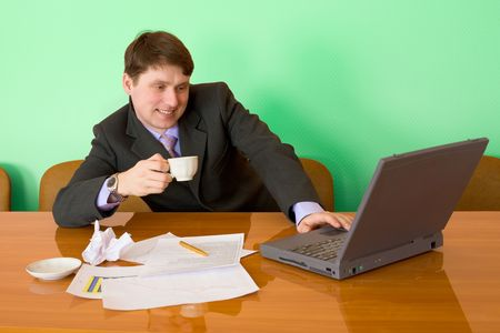 Businessman on a workplace with the laptop and a coffee cup Stock Photo - 4743160