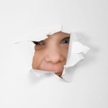 child's: Childs eye looking through hole in sheet of paper Stock Photo