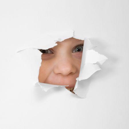 L'oeil de l'enfant regardant � travers le trou dans la feuille de papier Banque d'images - 4743112