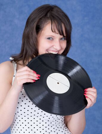 sound bite: Young woman and vinyl record on the blue background Stock Photo