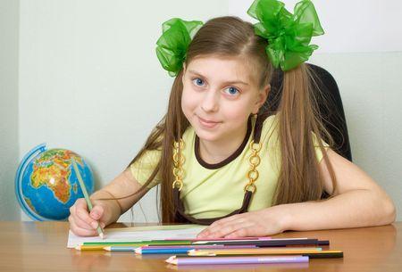 globe terrestre dessin: La jeune fille assise � une table avec des crayons de couleur