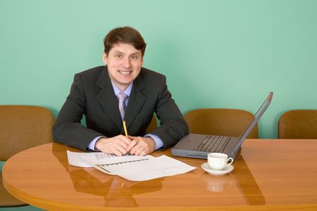 Businessman on a workplace with the laptop and a coffee cup photo