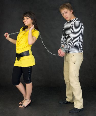 Lady guide shackled young man on the black photo