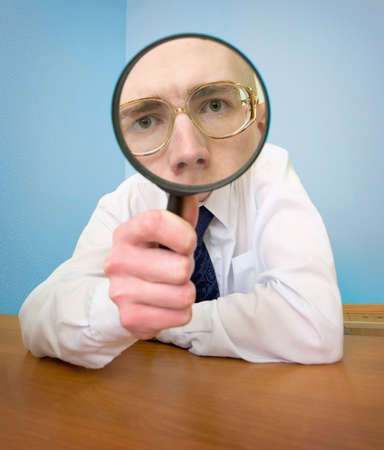 Man with a magnifier in a hand on a workplace photo