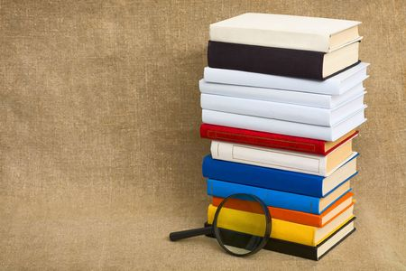Big pile of books and magnifier glass on canvas photo
